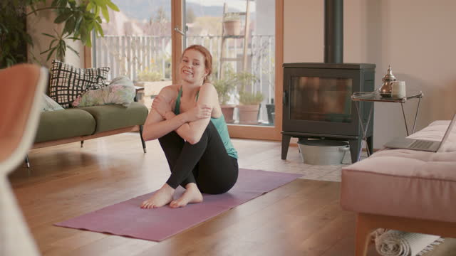 portrait of woman sitting on yoga mat at home smiling - pilates video stock e b–roll