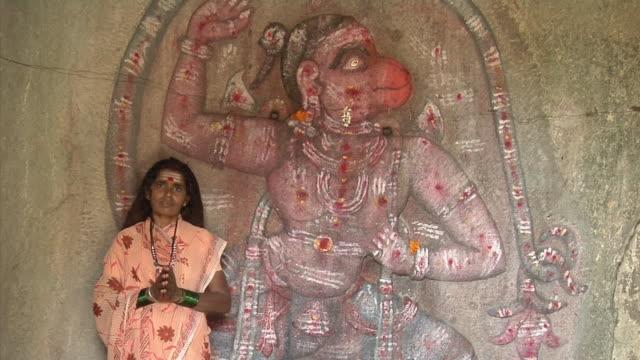 MS, Portrait of woman standing in front of carving of Hanumana, Hampi, Karnataka, India