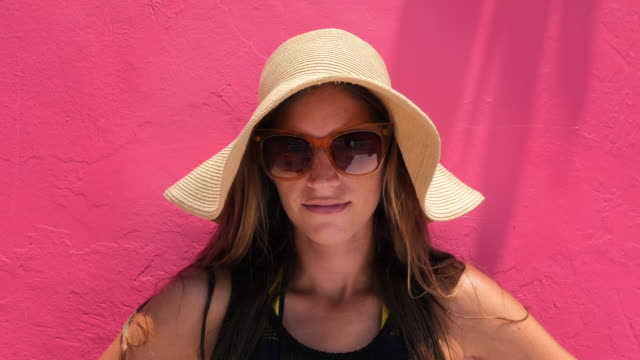 Portrait of woman standing in front of colorful wall wearing sunhat