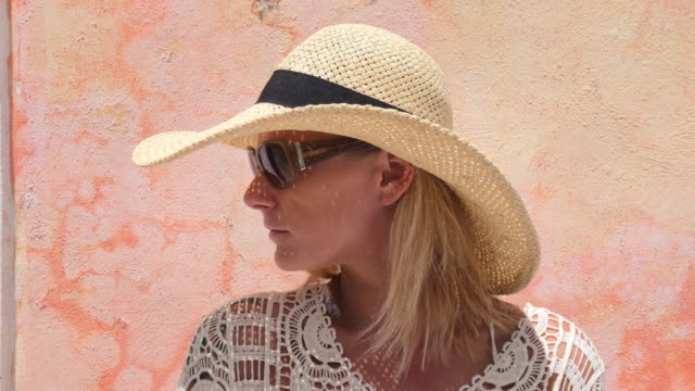 portrait of woman standing in front of colorful wall wearing sunhat  - sonnenhut stock-videos und b-roll-filmmaterial