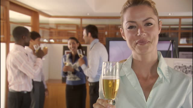 cu, selective focus, portrait of woman toasting with champagne  in conference room, colleagues in background, los angeles, california, usa - pardo brazilian stock videos & royalty-free footage