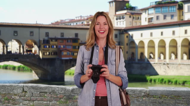 portrait of woman tourist in florence talking directly to camera - ponte点の映像素材/bロール
