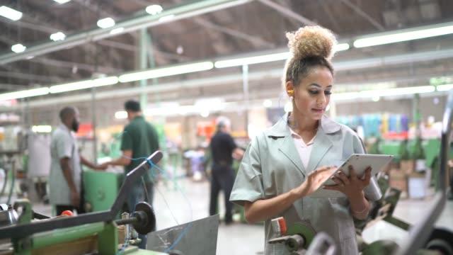 stockvideo's en b-roll-footage met portret van de vrouw met behulp van digitale tablet in de industrie - productielijn werker