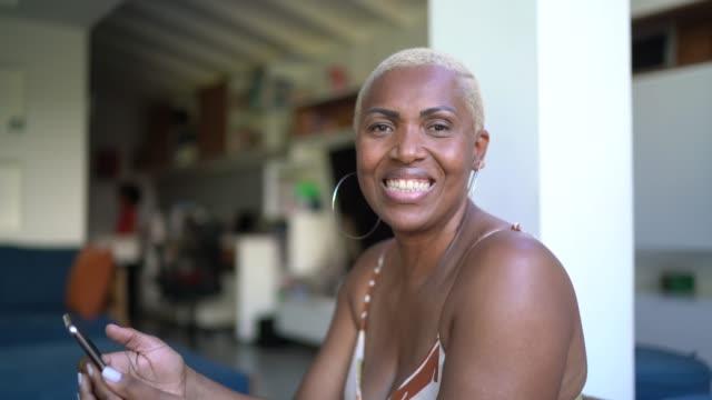 vídeos y material grabado en eventos de stock de retrato de mujer usando smartphone en casa - afro