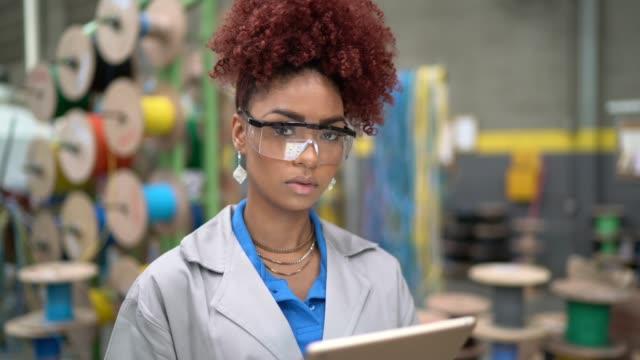 stockvideo's en b-roll-footage met portret van de vrouw met behulp van tablet werken in de industrie - productielijn werker