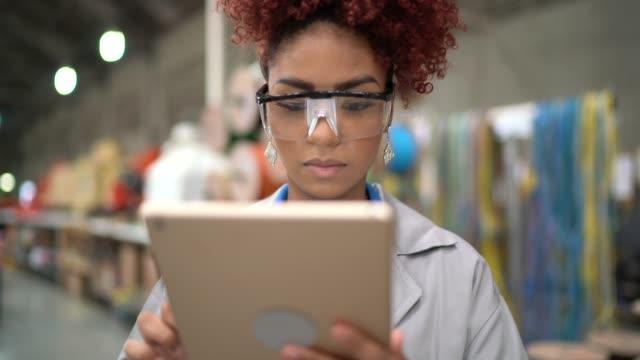 porträt einer frau, die tablets in der industrie verwendet - elektronik industrie stock-videos und b-roll-filmmaterial