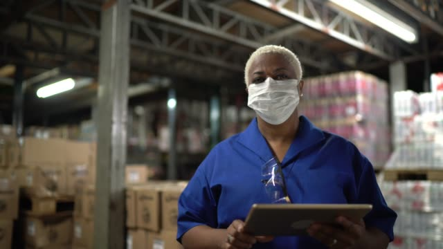 vídeos de stock e filmes b-roll de portrait of woman wearing face mask using digital tablet - working in warehouse / industry - fábrica