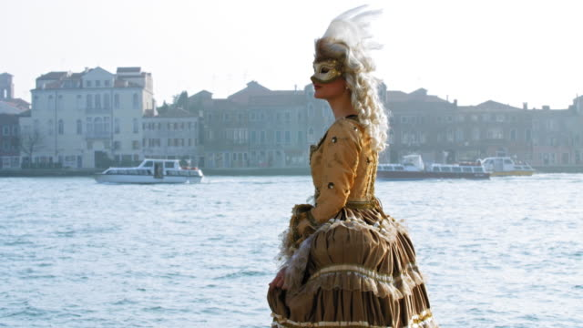 portrait of woman wearing historical clothing and carnival mask by canal, san giorgio maggiore church in background - historical clothing stock videos & royalty-free footage