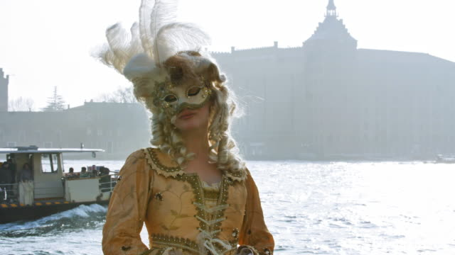 portrait of woman wearing historical clothing and carnival mask walking by canal - historical clothing stock videos & royalty-free footage