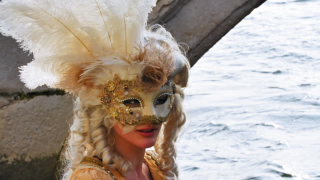 portrait of woman wearing historical clothing and carnival mask sitting by canal - historical clothing stock videos & royalty-free footage