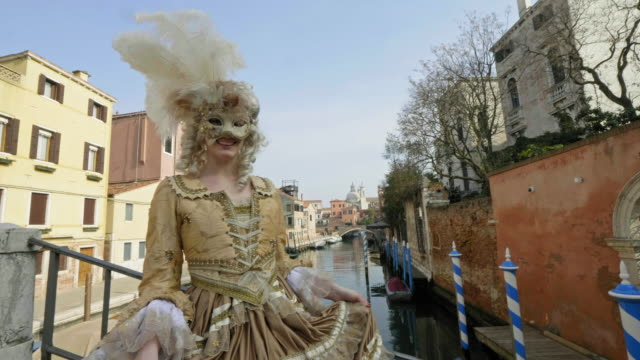 portrait of woman wearing historical clothing and carnival mask standing on bridge over canal - historical clothing stock videos & royalty-free footage
