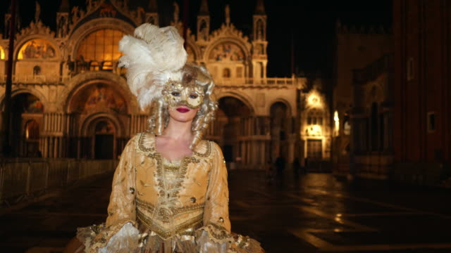 portrait of woman wearing historical clothing and venetian mask on st mark's square at night - gold dress stock videos & royalty-free footage