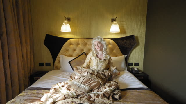 portrait of woman wearing historical clothing sitting on bed - historical clothing stock videos & royalty-free footage