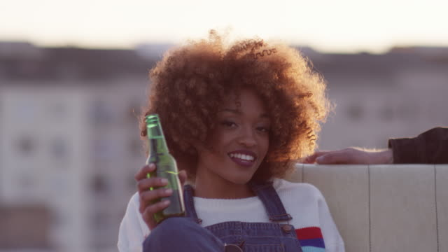 portrait of woman with beer bottle sitting on sofa - building terrace stock videos and b-roll footage