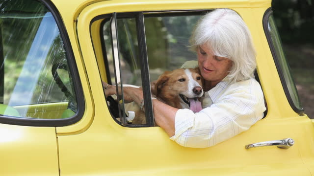 CU Portrait of woman with dog leaning out window of antique pickup truck, Richmond, Virginia, USA