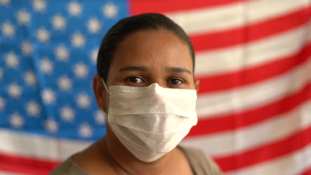 portrait of woman with face mask and american flag on background - north america stock videos & royalty-free footage