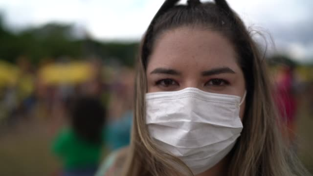 portrait of woman with facial mask in a public event - protective face mask stock videos & royalty-free footage