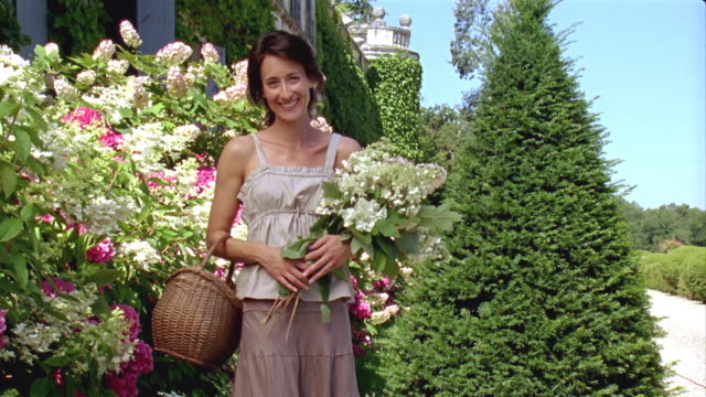MS, Portrait of woman with flowers in front of castle, Saint Ferme, Gironde, France