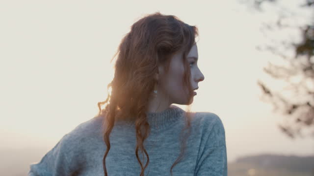 portrait of woman with long red curly hair at sunset - rotes haar stock-videos und b-roll-filmmaterial
