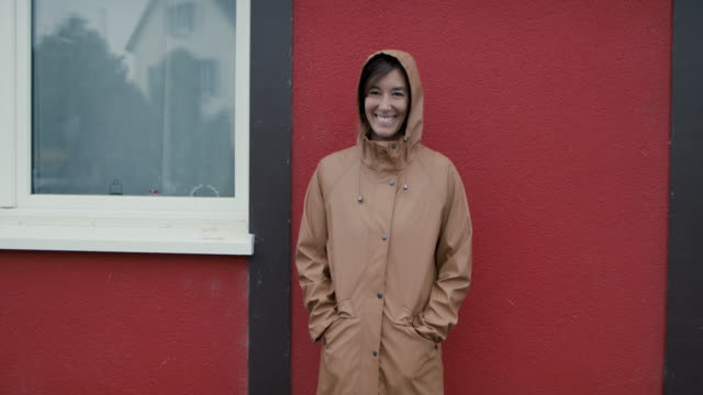 portrait of woman with raincoat smiling in front of red wall - レインコート点の映像素材/bロール
