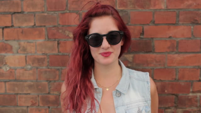 Portrait of woman with red hair in front of brick wall smiling into camera
