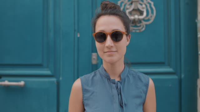 portrait of woman with sunglasses in front of blue door - brunt hår bildbanksvideor och videomaterial från bakom kulisserna