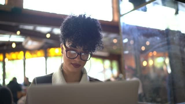 portrait of woman working on laptop at cafeteria / restaurant - financial technology stock videos & royalty-free footage