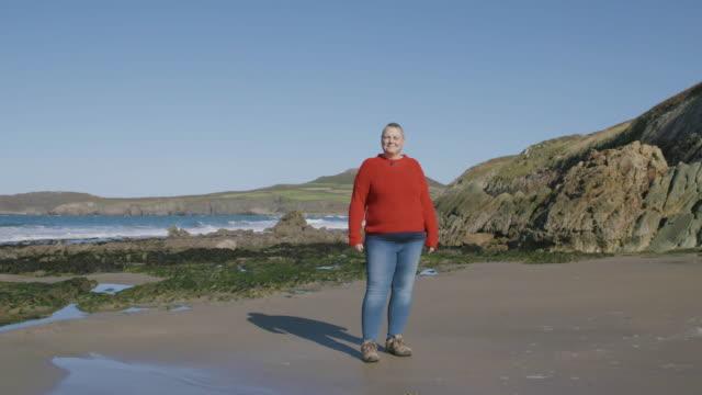 stockvideo's en b-roll-footage met portret van vrouwen staande op een leeg strand op zoek naar camera. - 45 49 jaar