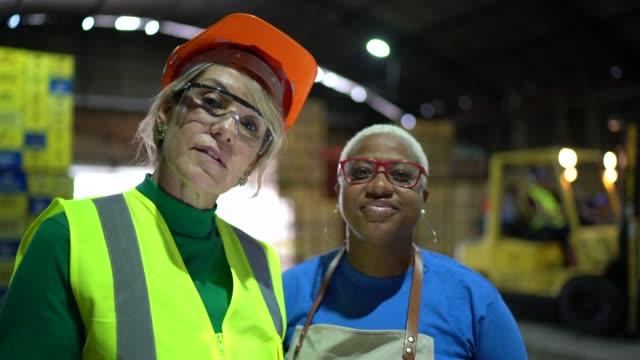 vídeos de stock, filmes e b-roll de retrato das mulheres que trabalham junto em um armazém - dedicação
