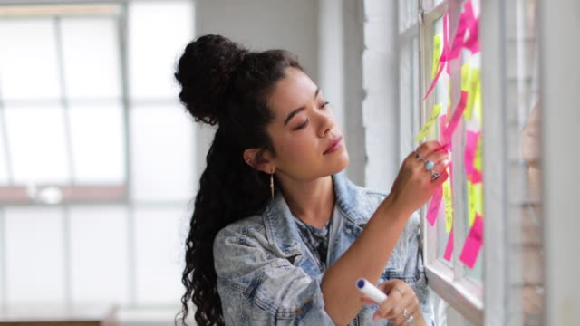 portrait of young adult female brainstorming in a creative office with adhesive notes - loft apartment stock videos & royalty-free footage