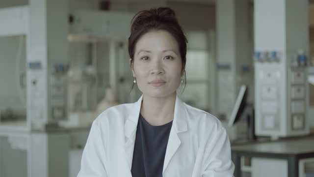 portrait of young adult female chinese doctor standing in science laboratory looking at camera pensive, wearing lab coat and stethoscope - one mid adult woman only stock videos & royalty-free footage