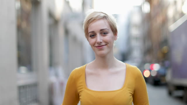 portrait of young adult female on street - sorridere video stock e b–roll