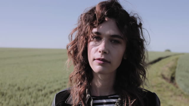 portrait of young adult woman in field looking to camera - leather jacket stock videos & royalty-free footage
