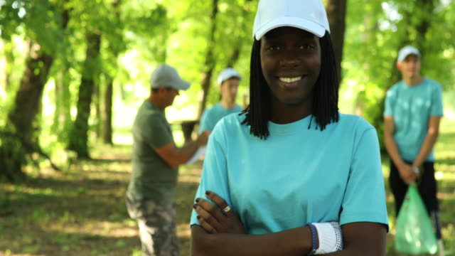 portrait of young african woman smiling while cleaning a public park - disability services stock videos & royalty-free footage