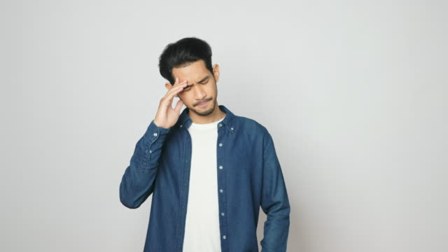 portrait of young asian man in disappointment facial expression while standing over grey background instudio, 4k resolution - guilt stock videos & royalty-free footage