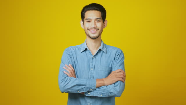 portrait of young asian man smiling and looking at camera while standing over yellow background in studio - comfortable stock videos & royalty-free footage