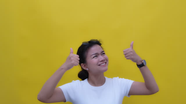 slo mo portrait of young asian with a happy smile giving two thumb up, looking up copy space- hand gesture on yellow background - yellow background stock videos & royalty-free footage