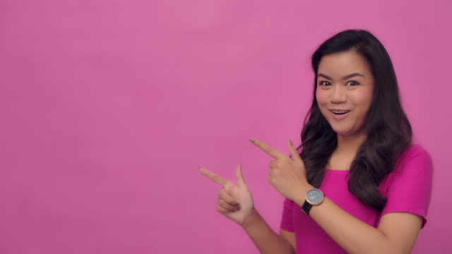slo mo portrait of young asian with a happy smile pointing at your logo- hand gesture on pink background - pink background stock videos & royalty-free footage