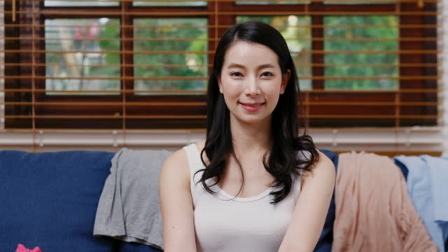 portrait of young asian woman smiling and looking at camera while sitting on sofa at home living room - mezzo busto video stock e b–roll
