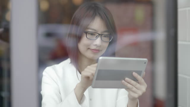 stockvideo's en b-roll-footage met portrait of young asian women sitting indoors in a lounge browsing the internet online using a digital tablet computer - middellang haar