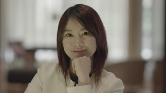 portrait of young asian women sitting indoors in a lounge - 中国人点の映像素材/bロール