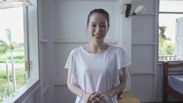 若い魅力的なアジアの若い女性の肖像画とカメラを見て - 中国人点の映像素材/bロール