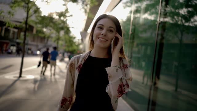 vidéos et rushes de portrait of young attractive caucasian women walking in the city talking on the phone. urban people lifestyle background - cheveux raides