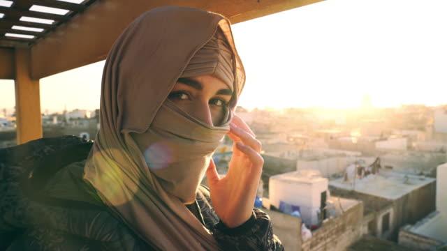 vidéos et rushes de verticale de jeune femelle musulmane attirante dans le hijab. regarder l'appareil photo - maroc