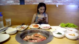 Portrait of Young Beautiful Asian Woman Happy Smiley using Mobile Phone for Chatting Social Media among Barbecue Grill on the Table.