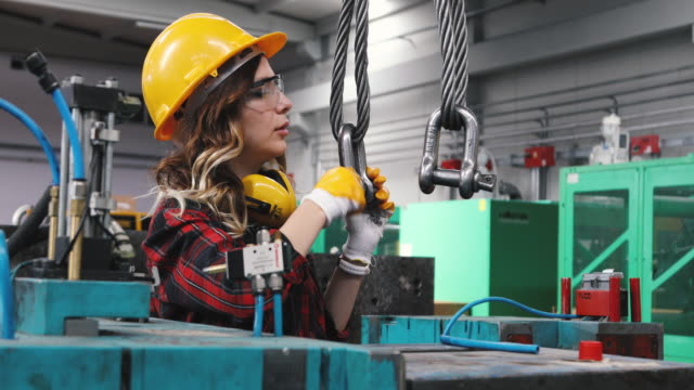 portrait of young beautiful engineer woman working in factory building. - dare la forma video stock e b–roll