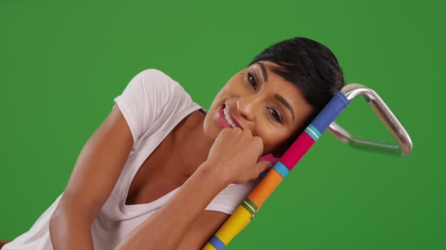portrait of young black female talking to camera and smiling on green screen - zurücklehnen stock-videos und b-roll-filmmaterial