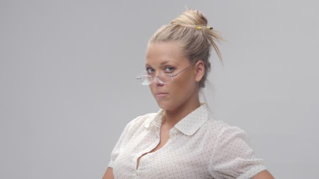 年輕的、 金髮碧眼的開朗的女人嘗試新眼鏡和製作的面孔的畫像 - 高清電視 影像的技術 個影片檔及 b 捲影像