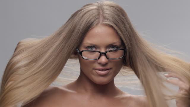Porträtt av unga, Blonda, gladlynt kvinna försöker nya glasögon och göra ansikten