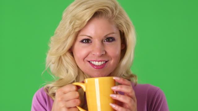 stockvideo's en b-roll-footage met portrait of young blond woman drinking from a cup  - natuurlijk haar